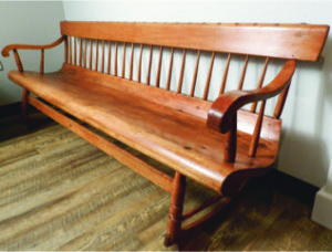 """An early 19th C. Quebec pine and birch rocking bench of outstanding colour with stick back and shaped seat, h. 28 1/2"""" x w. 78 1/2"""" x d. 17"""""""