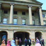 Mothers of Confederation wearing 1860 fashionable hoop skirts outside Province House. Women played an important role, hosting dinner parties and grand balls. Courtesy of Confederation Centre of the Arts P.E.I.