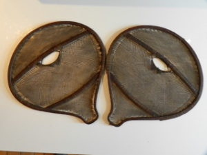 """A good pair of 19th Century beaver tail snow shoes, the fine sinew intricately woven to cover the pear shaped stretchers, retaining traces of red trade wool decoration, possibly Mohawk, h. 27"""" x w. 25""""."""