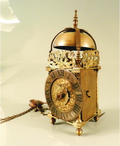 """A mid 17th Century English brass lantern clock with Roman numerals and engraved face, raised on 4 feet, has weights and pulley, 9"""" high."""