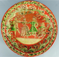 "An 18th Century Marburgh terracotta charger painted with a dancing couple in green and cream, dated 1772, with card verso dating it 1812, 20"" diameter."