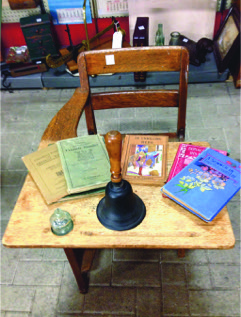 Early school desk, teacher's hand bell, various readers and books. Courtesy of Roadshow Antique Market, Pickering