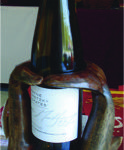Hand carved wine bottle holder featuring graceful dolphins. Offered by Bonnie Saveall. Contact Bonnie at Karen Brown Antiques, 613-396-6888