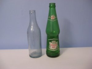 A clear glass early J. McLaughlin soda water bottle and green Canada Dry bottle
